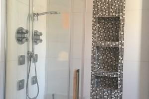 Douche en céramique avec niche et insertion de pate de verre. Douche pluie, douche-téléphone et plusieurs jets muraux font de cette douche une belle réussite.