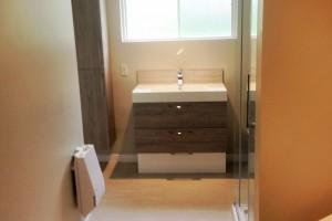 Rénovation d'une salle de bain avec espace pour les laveuses sécheuses. Nouvelles armoires et vanité, douche en céramique avec portes en verre. Pose d'un plancher de céramique.