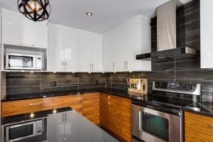 Cuisine avec armoire thermoplastique blanc et armoire en noyer. Les comptoirs sont en granite et le dosseret en céramique.