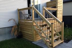 Balcon en bois traité avec mur d'intimité et poteau de rampe tubulaire noir.