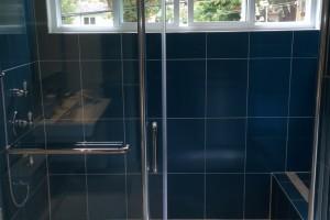 Rénovation d'une salle de bain. Installation d'une grande douche en céramique avec porte en verre. Agrandissement de la fenêtre.
